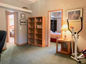 Room with dark green carpet showing open doors to 2 bedrooms; there's a small table with lamp, a stair-stepper exercise machine, and a mostly empty bookshelf