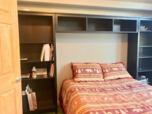 Full-size bed with reddish spread; there's a big black bookcase built up and around it against the wall