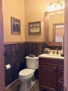 Half bath with dark wood wainscoting, vanity with dark cupboard doors, and 2 old vintage photos on the wall