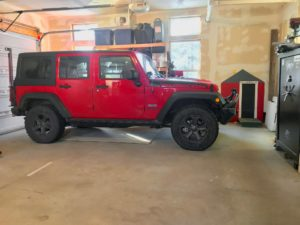 Big garage with concrete floor, large black safe, and bright red Jeep Wrangler