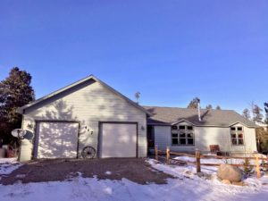 Front of light green ranch house with 2-car garage, gravel driveway, and snow in yard