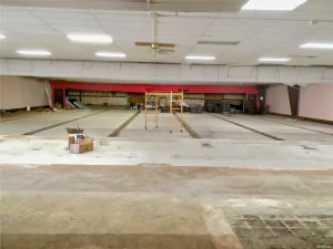 Huge interior space with concrete floors and gutters; bowling lanes are gone