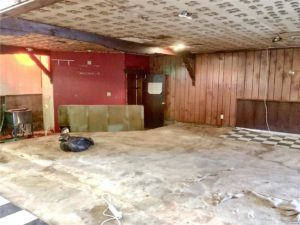 Not quite sure what's going on in this room… floor and ceiling are all torn up, but there are a few black-and-white checkered tiles left. Walls are mostly wood planks but there is a small section painted bright red.