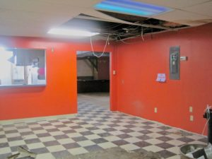 Room with bright red walls and black-and-white checkered floortiles; parts of the ceiling are gone or hanging down. Very classy.