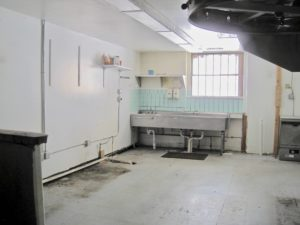 Industrial kitchen with big sink, white walls, and lots of light coming in through the window