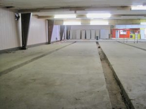 Photo of bowling alley interior taken from where the pins would have been, looking back at customer area. No more lanes; just concrete floor and gutters