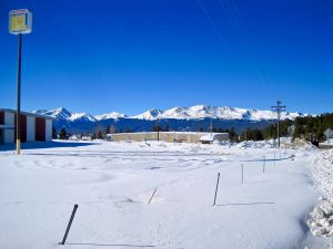 Exterior shot focusing on snowy parking lot and mountains in the background; bowling alley sign is visible to the left