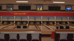 View from scoring area showing about 10 lanes with pins set up; above the lanes are three TVs, two big speakers, and red and blue paint