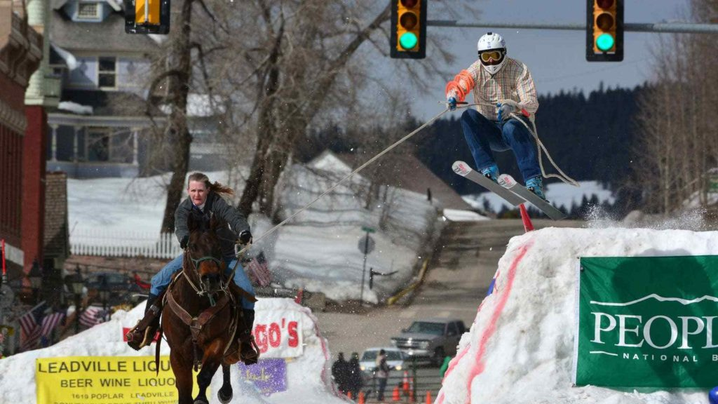 Skijoring in Leadville! A woman rides a galloping horse pulling a skier behind, who is coming up off a jump